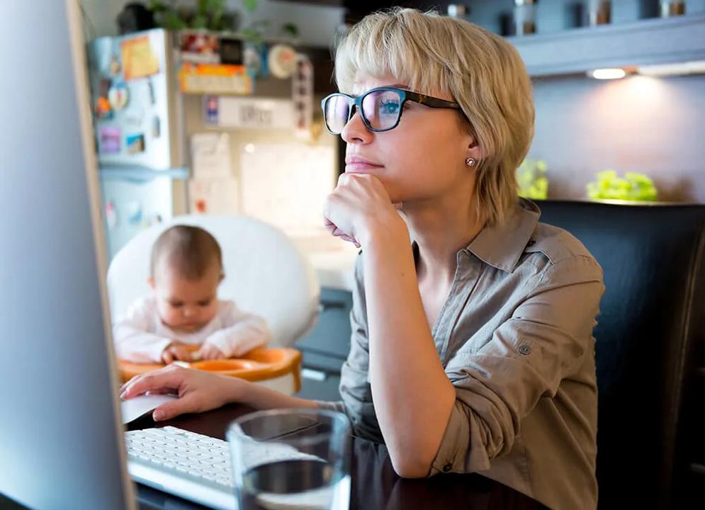 Mujer trabajando desde casa con su hijo a su lado. © iStock